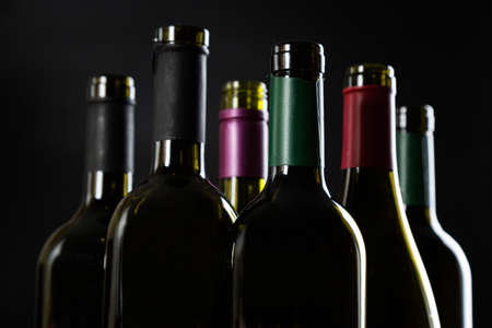 several open Bottles of wine are in a row on a dark glossy background. Archivio Fotografico