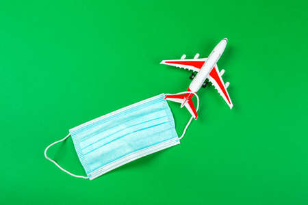 Airplane model with a blue medical mask. online ticketing and tourism concept during pandemic