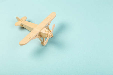 Model of a wooden toy plane, airliner, on a blue background. travel and transport concept