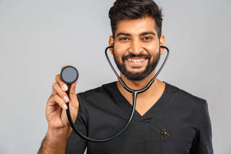 amusing young indian doctor or surgeon with stethoscope on gray background
