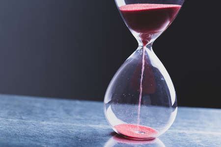 Hourglass as a concept of passing time for business deadline, urgency and outcome of time. Banque d'images