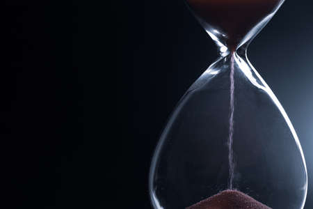 Sand passes through hourglass bulbs measuring the transit time counting down to the deadline, against a dark background