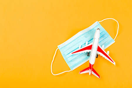 Airplane model with a blue medical mask. online ticketing and tourism concept during covid pandemic
