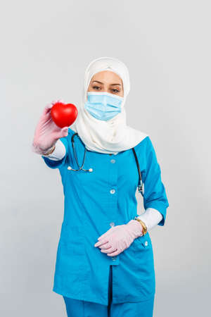 friendly Muslim doctor or nurse in hijab, mask, gloves holding a red heart on a gray background.