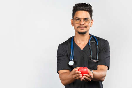 young Indian / Asian doctor with stethoscope in uniform on a gray background holding a red heart in his hands. medicine and cardiology concept
