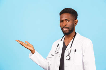 African American male doctor with stethoscope in a white coat shows with his hands to the place for text on a blue background. medicine and healthcare concept.