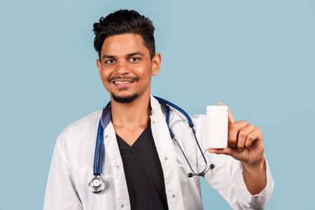 handsome young Indian / Asian doctor with stethoscope holding a jar of pills in his hand on a blue background. disease. 免版税图像