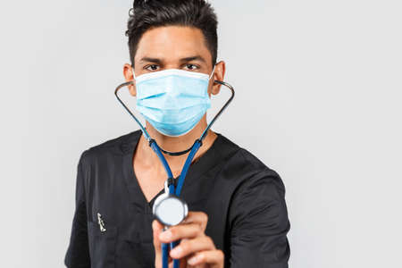 Handsome modern Indian / Asian doctor with stethoscope, in medical facial mask on gray background. protection against medicine, healthcare 免版税图像