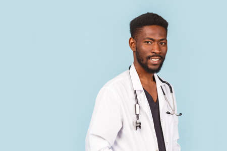 medicine, profession and healthcare concept. African American male doctor or scientist in white coat against blue background