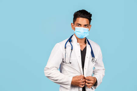 handsome young Indian / Asian doctor with a stethoscope, in a medical mask in a white coat on a blue background. new diseases