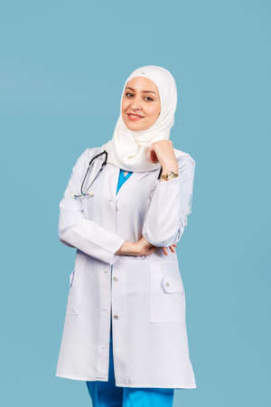 Portrait of a friendly, Muslim doctor or nurse woman in hijab with a stethoscope in a white coat. on a blue background. medicine and healthcare 免版税图像