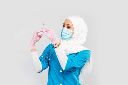 Portrait of a friendly Muslim doctor or nurse in hijab and medical face mask holding a syringe on a gray background. the concept of vaccination of the population or injection plastic of the face
