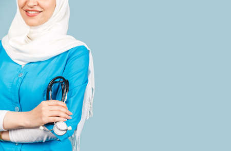 Portrait of a friendly, muslim doctor or nurse woman in hijab with a stethoscope on a blue background. health worker