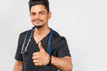 young Indian doctor or surgeon with stethoscope shows thumb up on gray background. medicine and healthcare concept