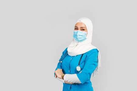 Portrait of a friendly Muslim doctor or nurse wearing hijab and medical face mask and gloves on a gray background.