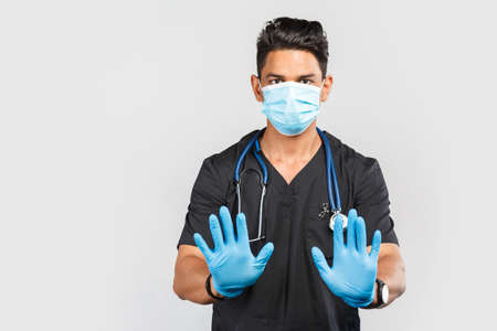 Handsome modern Indian / Asian doctor with stethoscope wearing blue medical face mask and gloves on gray background. 免版税图像