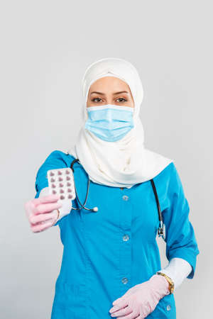 Portrait of a friendly Muslim doctor or nurse in a hijab, mask, gloves offering a pill to the patient on a gray background. 免版税图像