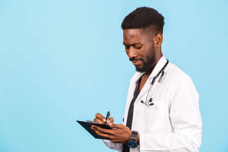 African american male doctor with stethoscope in white coat writing prescription on blue background