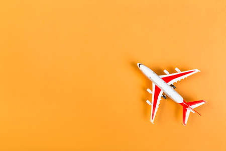 toy Model of a modern airplane with red wings. tourism and travel concept. orange background