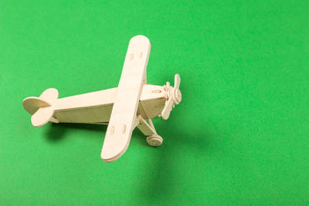 Model of a wooden toy plane, airliner, on a green background. the concept of travel