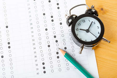 answer sheet, test in exercise and passing examination paper computer sheet with pencil alarm clock and pencil for education concept