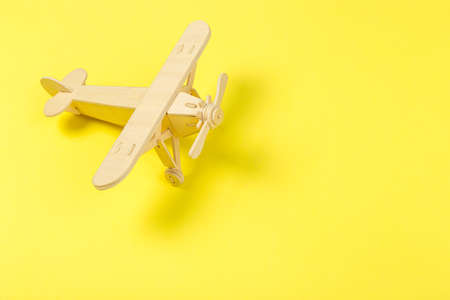 Model of a wooden toy plane, airliner, on a yellow background. travel and tourism concept, air travel