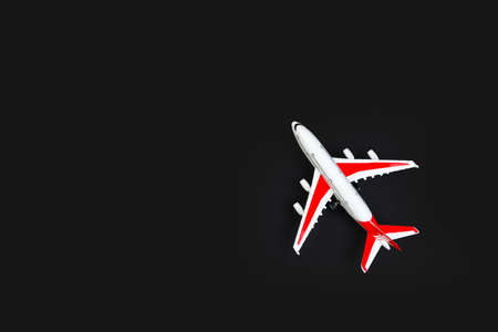 plastic model airplane with red wings against a dark background. tourism and travel concept. 免版税图像