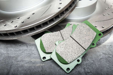 brake pad and Perforated brake discs on a dark gray table