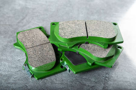 A set of four new car brake pads on a gray background.