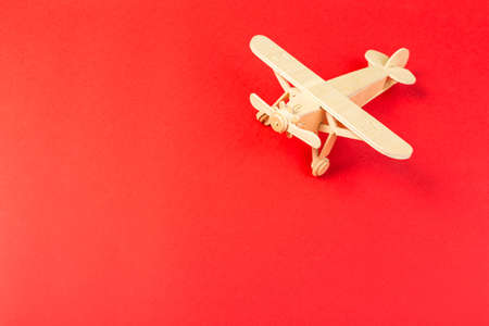 wooden model of a passenger plane with on a red background. tourism and travel concept.