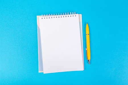 multiple school notepad on blue background, spiral notepad with blank page and ballpoint pen on table top view 免版税图像