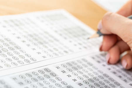 The student fills in the answers to the test in the exercise and examination paper with a pencil. education concept.