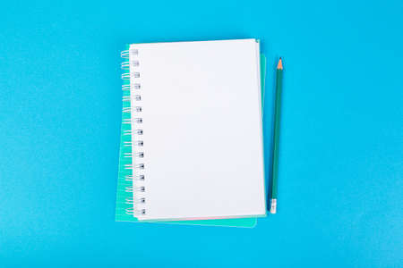 several school notebooks on a blue background, spiral notepad with a blank page and a pencil on the table top view