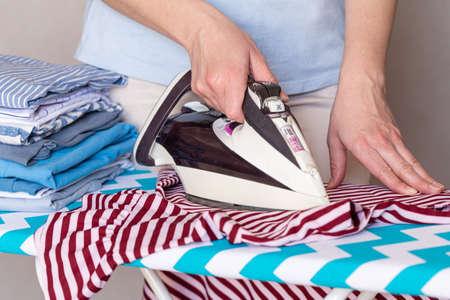 Woman ironing clothes on ironing board, close up 版權商用圖片