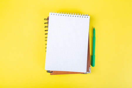 open spiral notepad on a yellow background with a pen. top view, stack of notepad with blank sheet. school concept, businessman work desk.