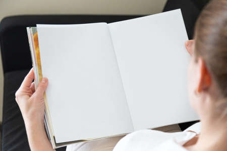 Beautiful female hands hold an open book or magazine in a room on a black sofa 版權商用圖片