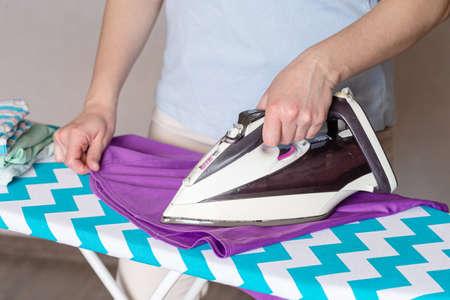 Female hands ironing white shirt collar on ironing board