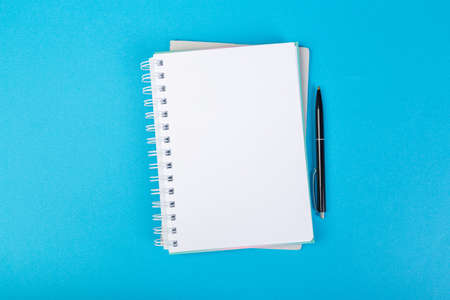 multiple school notepad on blue background, spiral notepad with blank page and ballpoint pen on table top view 版權商用圖片