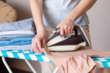 Woman ironing clothes on ironing board, close up 版權商用圖片