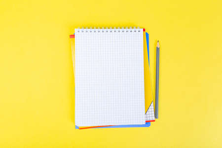 open notepad on yellow background with pencil on top, spiral notepad with blank sheet. top view of school concept, work desk of businessman.