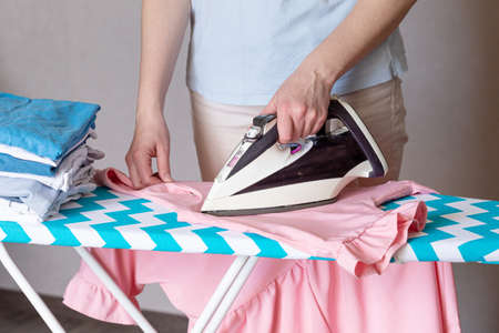 Female hands ironing white shirt collar on ironing board