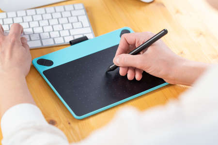 A graphic designer works on a digital tablet. work from home
