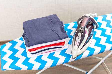 Folded ironed men's shirts lie next to the iron on the ironing board. Фото со стока