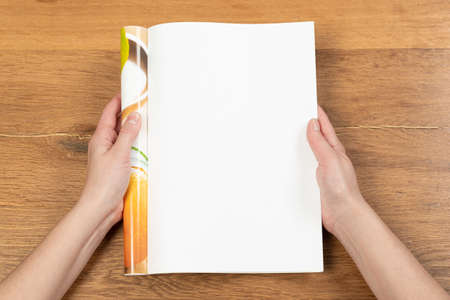Woman's hands open empty catalog, magazines, book mockup on wooden table Фото со стока