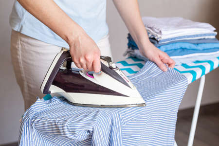 Woman ironing clothes on ironing board, close up Фото со стока