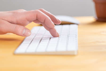 Woman office worker typing on white keyboard