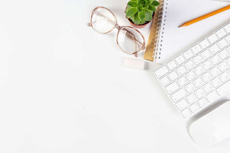 White office desk with blank laptop, computer keyboard and other stationery, potted plant. Top view with copy space, top view Фото со стока