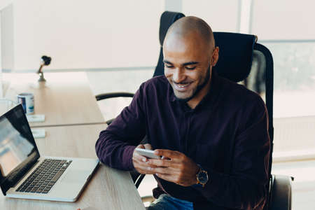 Smiling bearded african man using laptop at home, sitting on a wooden table. Concept of young people work mobile devices. Blurred window background, wide.