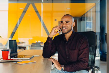 Confident young african american businessman working on laptop and talking on a cell phone while sitting at his workplace in startup office