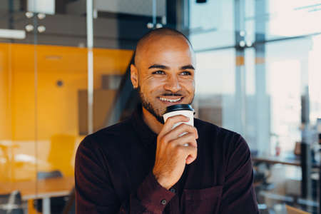 Happy african american businessman with coffee in hands at modern office
